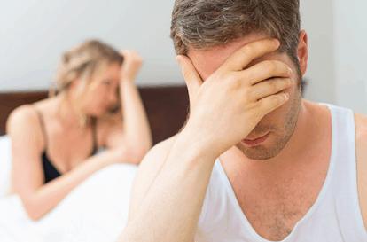Verzweifelte blonde Frau und verzweifelter dunkelhaariger Mann sitzen im Bett und halten sich beide die Hand vor die Stirn