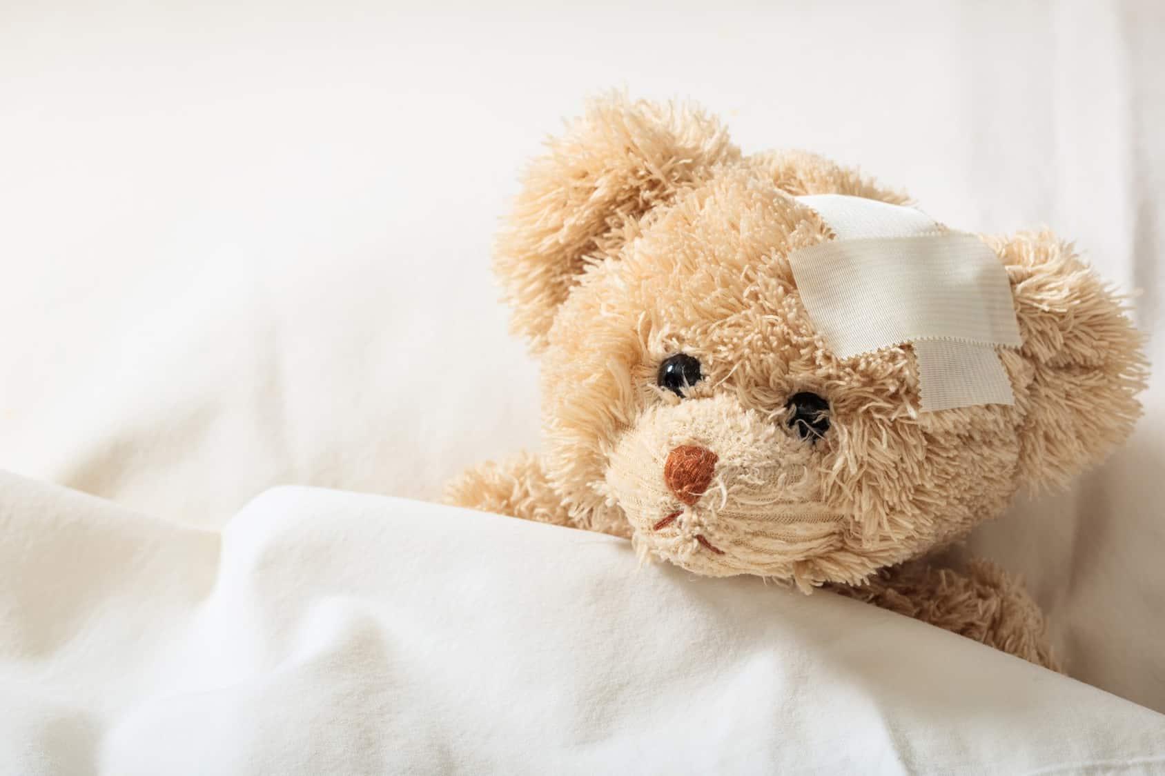 Beiger Teddybär liegt im Bett und hat ein Pflaster auf der rechten Stirn