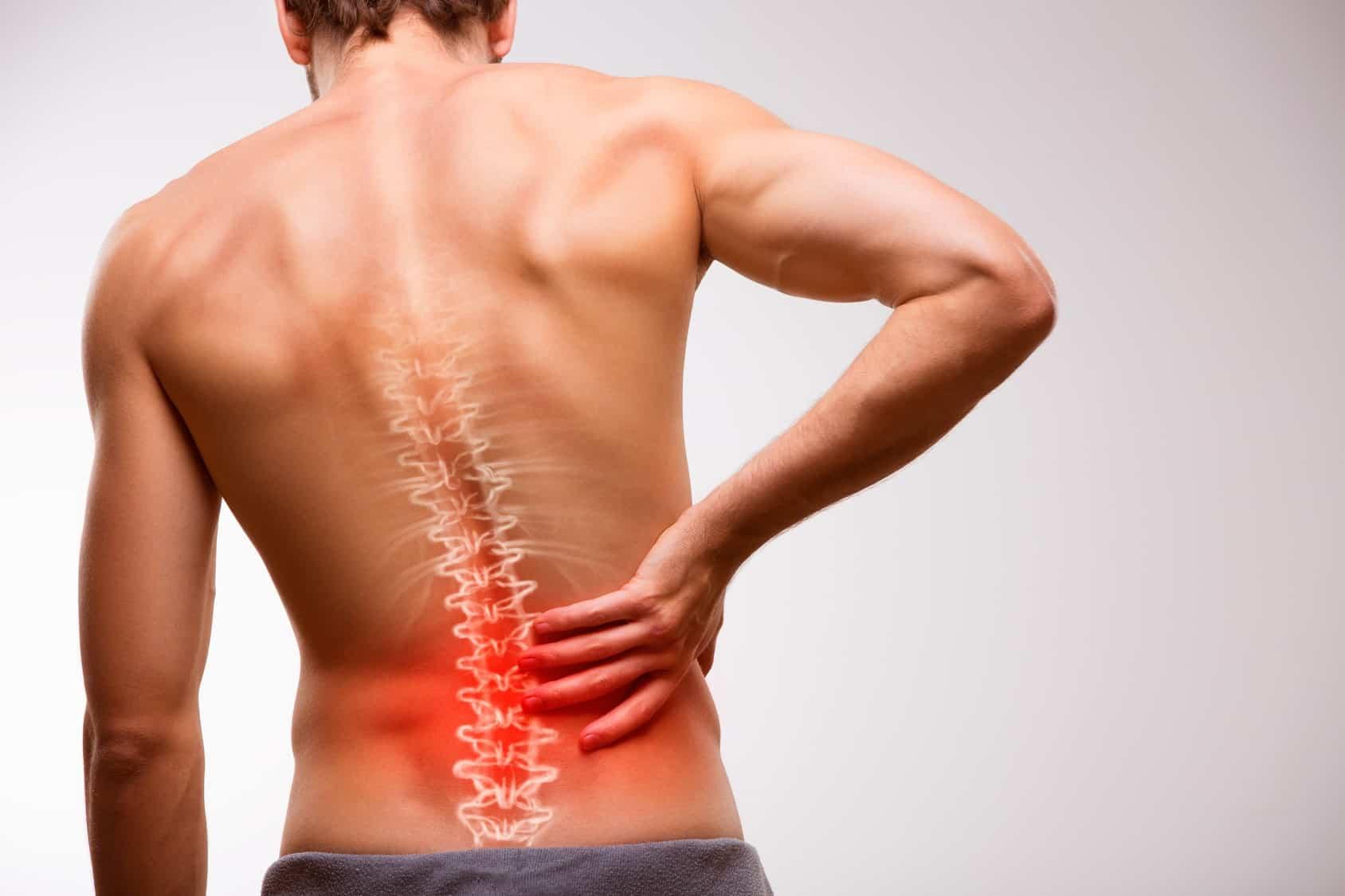 Mann steht vor einer Wand, es ist der Rücken zu sehen und es werden Schmerzen durch rote Farbe signalisiert