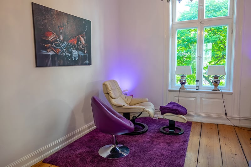 Therapiezimmer für Hypnose Hamburg mit weißem Ledersessel, lila Teppich und violettem  Barsessel und Holzdielen