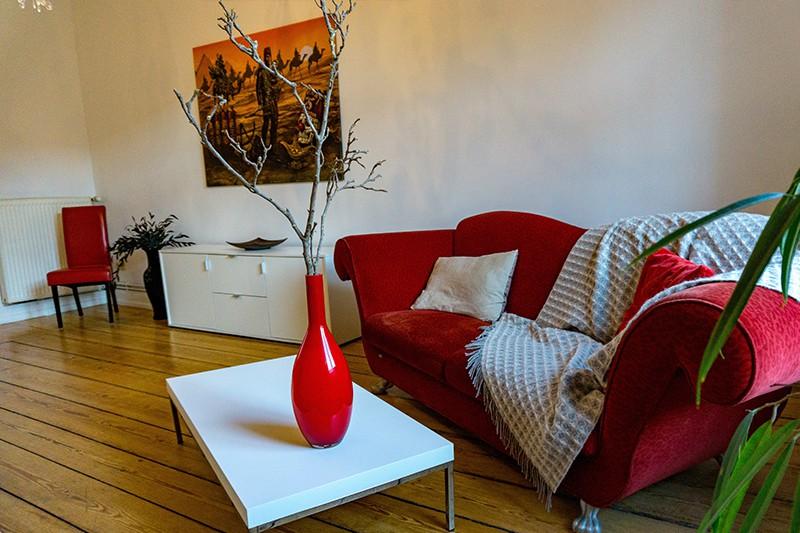 Wartezimmer für Hypnose Hamburg mit roter Couch, weißem Couchtisch mit roter Vase und Holzdielen